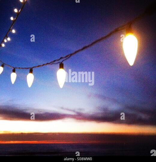 Lit up Holiday/Christmas lights hang with sun setting in the background. Manhattan beach, California USA. - Stock-Bilder
