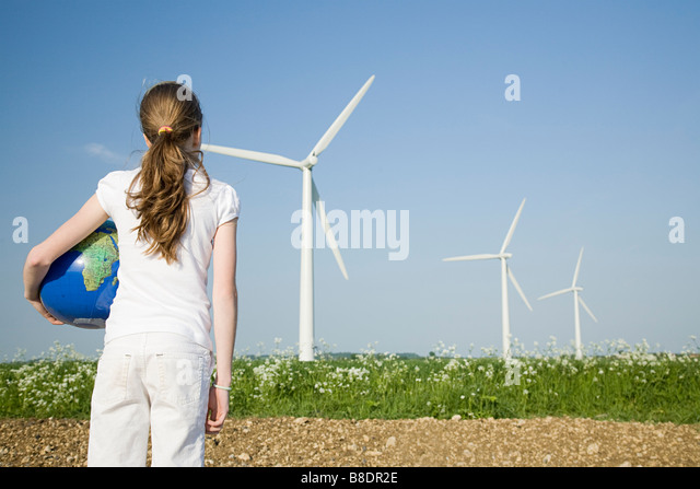 Girl with globe by wind turbines - Stock Image