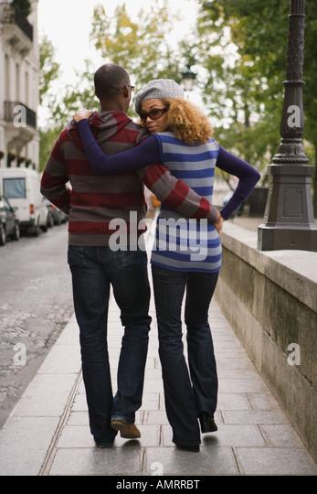 Rear view of African couple walking - Stock-Bilder