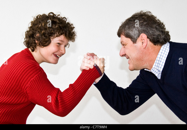 Father and son arm wrestling - Stock Image