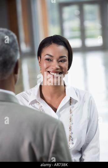 African businesswoman smiling at coworker - Stock-Bilder
