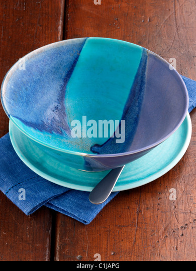 Turquoise empty craft pottery bowl on a wooden background - Stock Image