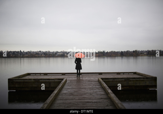 A woman wearing all black and holding an orange umbrella stands on the edge of a dock on a grey and cloudy day in - Stock Image