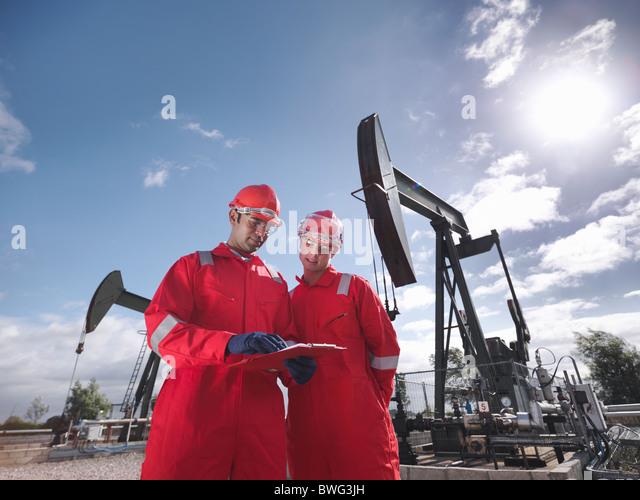 Two workers in front of oil wells - Stock-Bilder