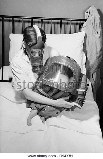 A mother and baby both in gas-masks during 1941. D3918 - Stock-Bilder