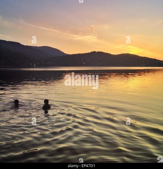 Two boys swimming in sea at sunset, Hof, Vestfold, Norway - Stock Image