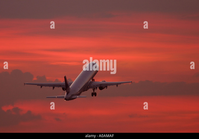 Aeroplane taking off against red sky. - Stock Image