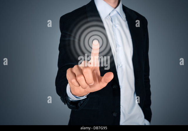 Portrait of business person touching button on invisible screen. Touch screen concept image. Isolated on dark gray - Stock Image