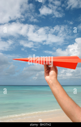 A man's hand holding a paper plane in the air on a tropical deserted beach - Stock Image