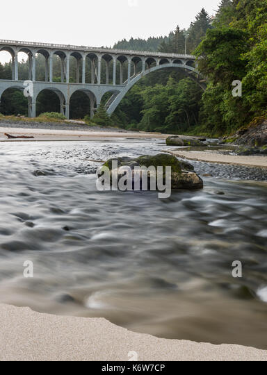 Water Runs in Creek Toward Pacific Ocean below highway 101 - Stock Image