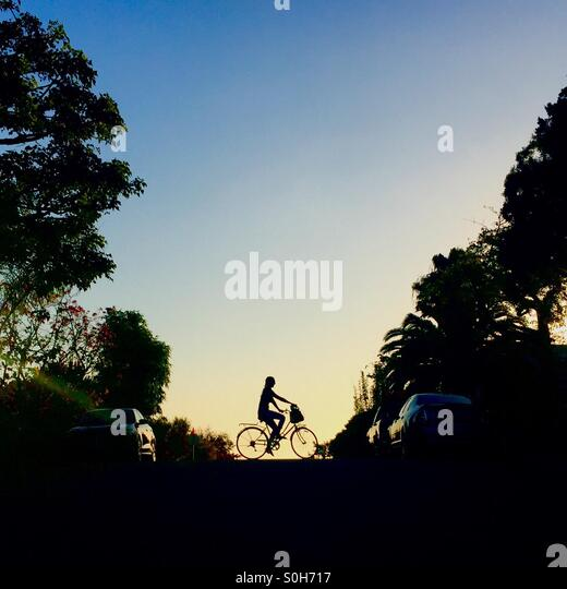 Silhouette of a girl riding a bike - Stock-Bilder