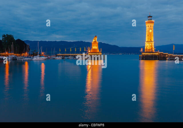 View of harbor entrance and lighthouse at night in Lindau at lake Constance, Bavaria, Germany - Stock Image