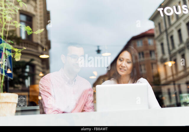 Sweden, Uppland, Stockholm, Man and woman talking in cafe - Stock Image