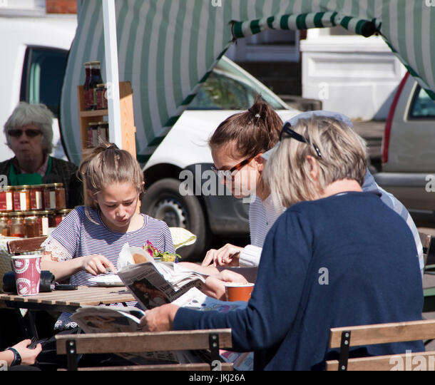 Teenage girls eat whilst mother reads newspaper - Stock Image
