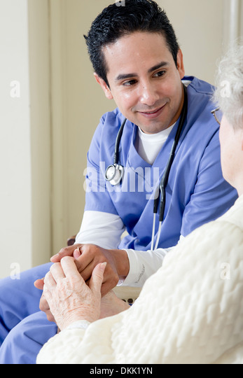 Male nurse assisting elderly patient - Stock Image