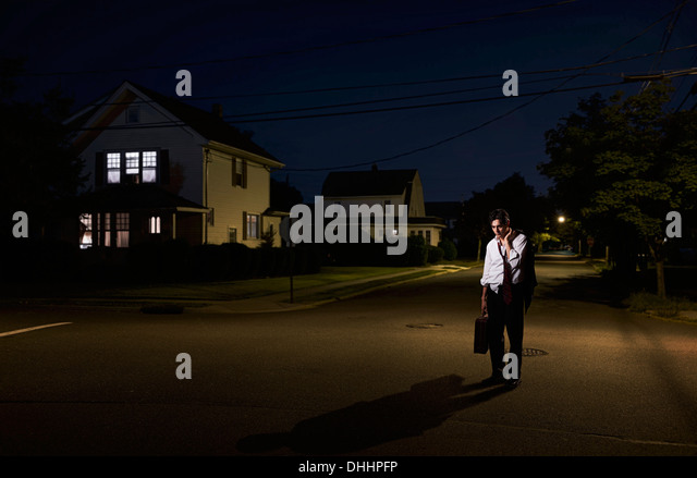 Tired business man coming home late at night - Stock Image