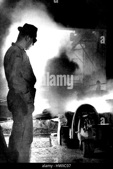 A worker looks on while a large smelter is used to melt down and recycle parts from telephones and other equipment - Stock Image