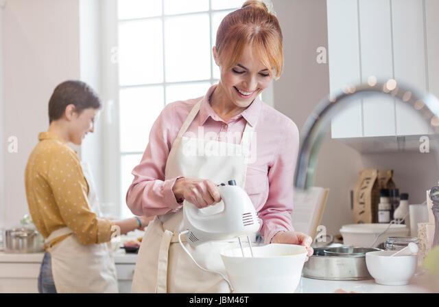 Smiling female caterer baking, using electric hand mixer in kitchen - Stock-Bilder