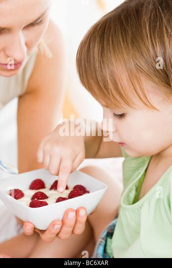 small girl eating breakfast - Stock-Bilder