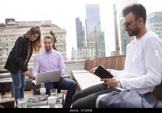 Businessman reading book while colleagues using laptop at rooftop restaurant - Stock-Bilder