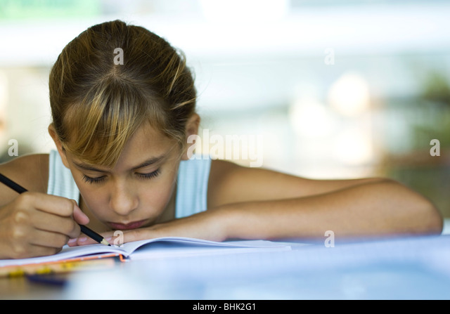Female junior high student writing homework assignment - Stock Image
