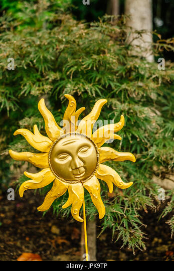 A garden decoration in the shape of the artistic shape of the sun set against a backdrop of green foliage. - Stock Image