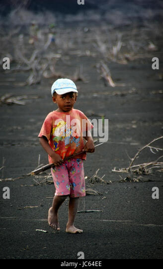 A young boy carries a machete across the ash left by volcano Mt. Tavurvur near Rabaul, Papua New Guinea. Most of - Stock Image
