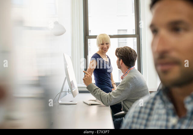 Three business colleagues in an office, two talking and one standing by the door listening. - Stock Image
