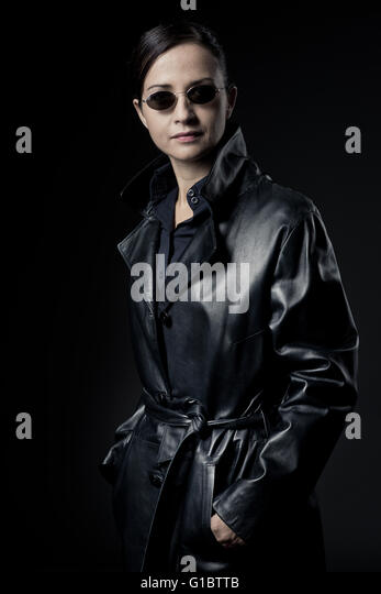 Attractive confident female agent in black leather coat with sunglasses. - Stock Image