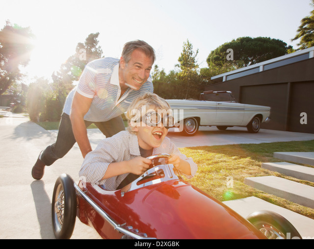 Father pushing son in go cart - Stock Image