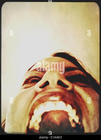 Looking up at woman's face from below - Stock-Bilder