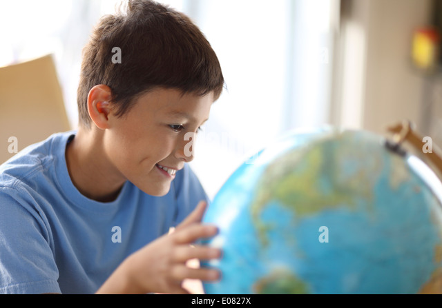 Y0oung boy dreams of traveling as he looks at a globe - Stock Image