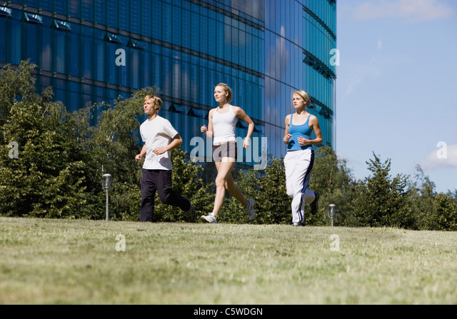Germany, Berlin, Three persons jogging - Stock Image