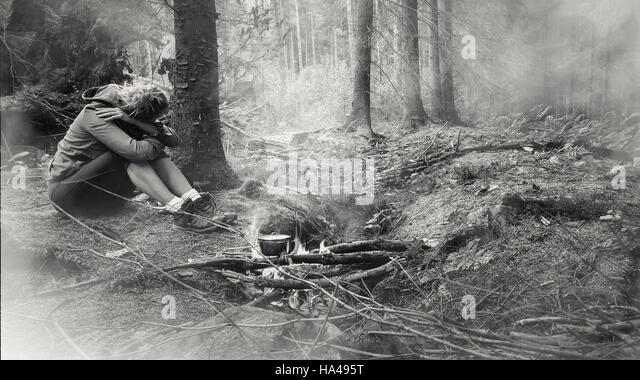young woman sitting in the forest alone by the fire - Stock Image