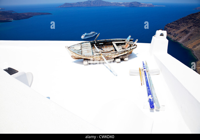 Thira, Santorini, Greek Island, Cyclades, Greece, old rowing boat in foreground of caldera on white washed building - Stock Image