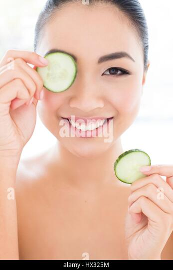 MODEL RELEASED. Young Asian woman holding cucumber in front of eye, portrait. - Stock-Bilder