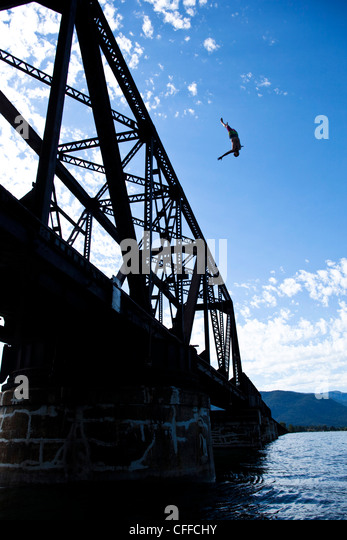 A athletic man flipping off a huge bridge on a sunny day in Idaho. - Stock Image
