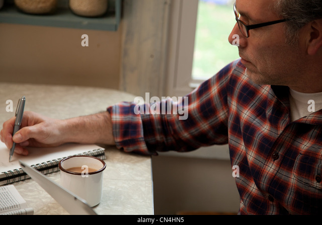 Mature man taking notes at home - Stock Image
