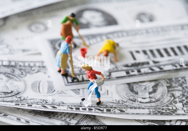 Miniature cleaning ladies washing play money - Stock Image