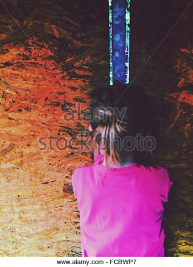 Rear View Of Girl Standing Against Wall - Stock Image