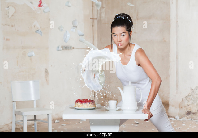 Woman pouring milk over set table - Stock Image