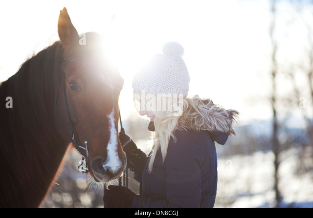Young woman with horse in winter - Stock Image