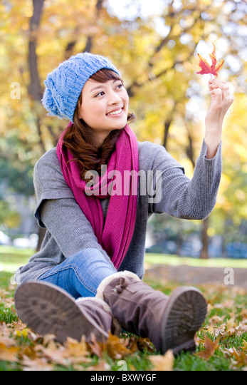 Young Woman Looking At Maple Leaf - Stock Image