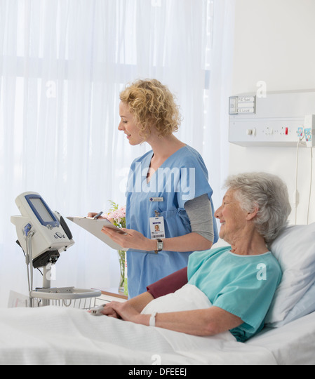 Nurse checking equipment in aging patient's hospital room - Stock Image