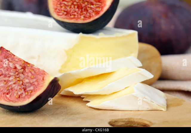 cheese and sweet fruit  figs on a wooden board - Stock Image