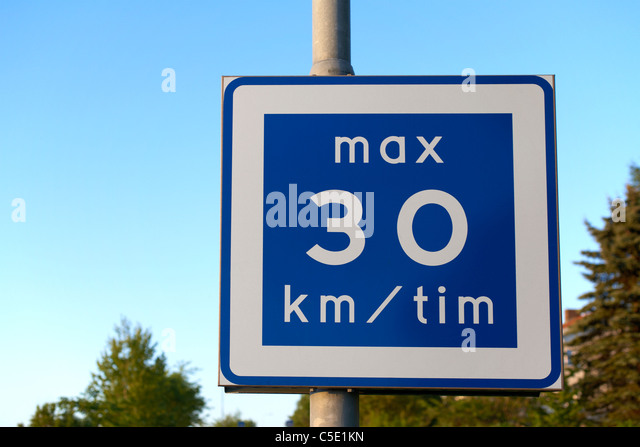 Close-up of a road sign on pole against blue sky - Stock Image