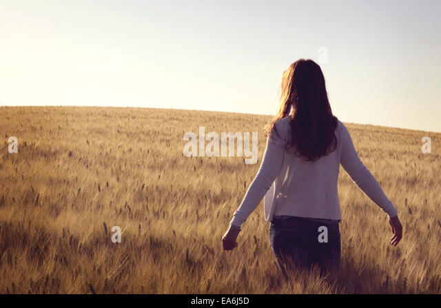 Woman standing in wheat field - Stock Image