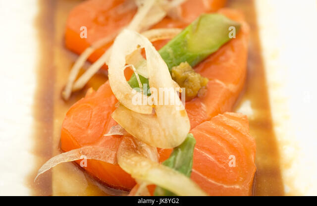 Salmon Sashimi with asparagus and onion on plate, ready to eat. - Stock Image
