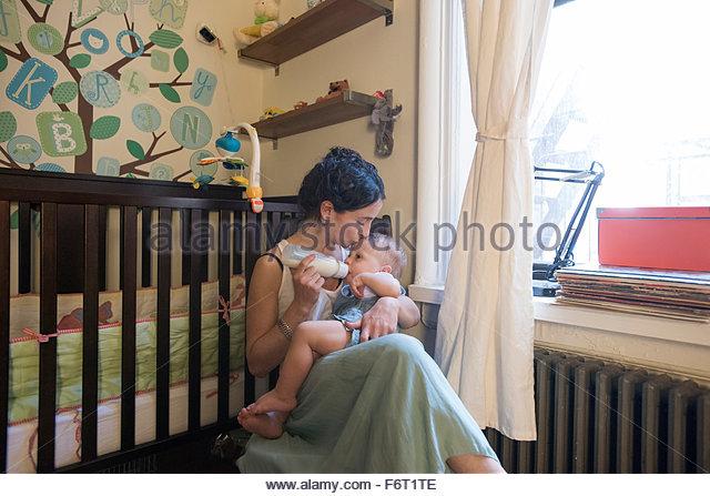 Caucasian woman feeding son in nursery - Stock-Bilder