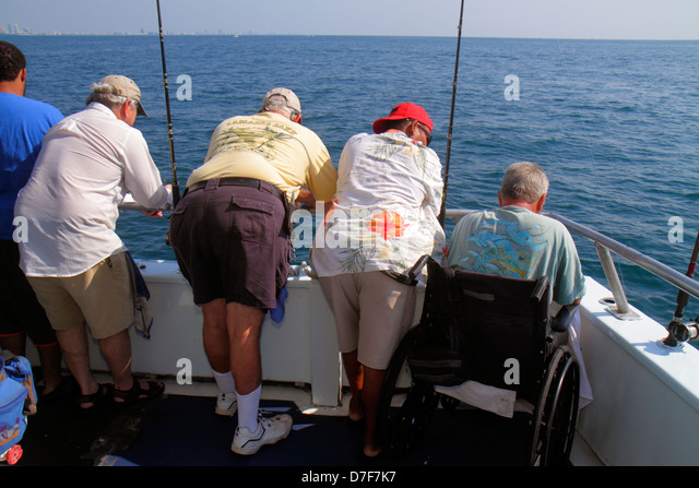 Miami Beach Florida Atlantic Ocean water charter fishing boat onboard man wheelchair disabled waiting rods deep - Stock Image
